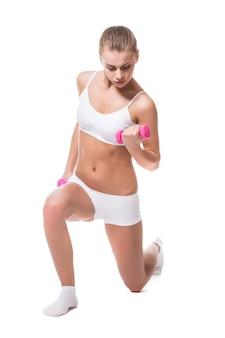 Mujer joven sosteniendo un dummbell, aislado sobre fondo blanco.
