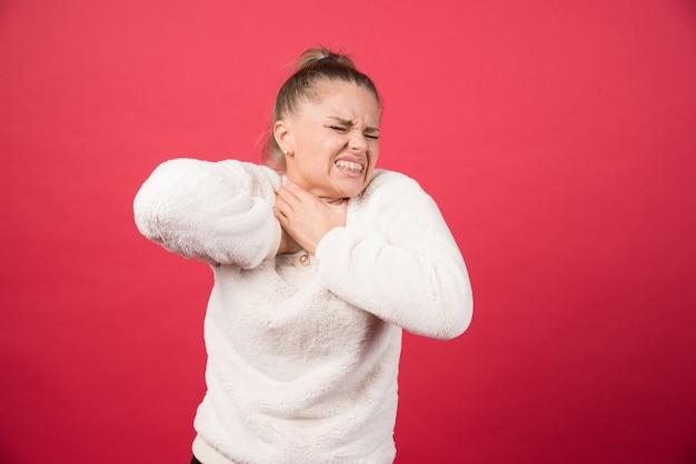 Una mujer joven sosteniendo la garganta y sufriendo de dolor.