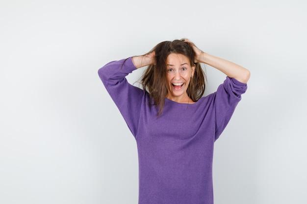 Mujer joven sosteniendo el hilo en las manos en camisa violeta y mirando loco. vista frontal.
