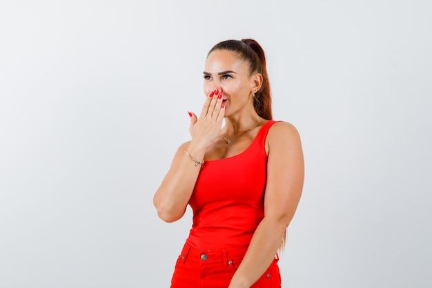 Mujer joven sosteniendo la mano en la boca en camiseta roja, pantalones y mirando asombrado. vista frontal.