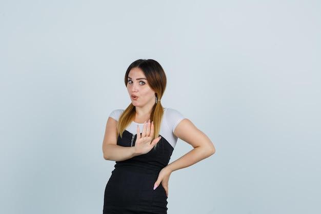 Mujer joven sosteniendo la mano en la cadera mientras muestra la señal de stop