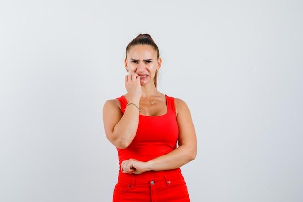 Mujer joven sosteniendo la mano cerca de la boca en camiseta sin mangas roja, pantalones y mirando asustado, vista frontal.
