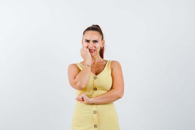 Mujer joven sosteniendo la mano cerca de la boca en vestido amarillo y mirando asustado, vista frontal.