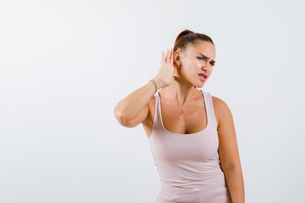 Mujer joven sosteniendo la mano detrás de la oreja en camiseta y mirando desconcertado, vista frontal.