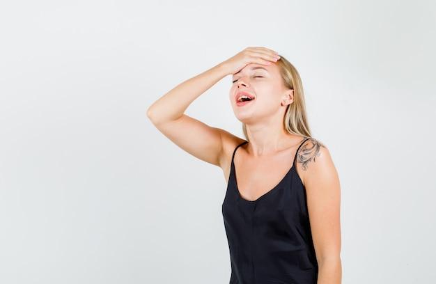 Mujer joven sosteniendo la mano en la frente en camiseta negra y mirando positiva.