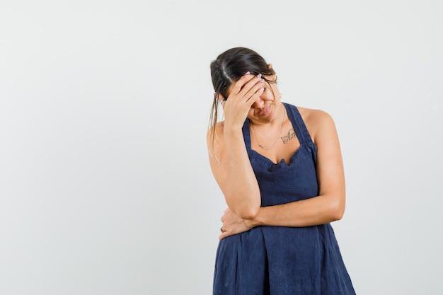 Mujer joven sosteniendo la mano en la frente en el vestido y mirando angustiado