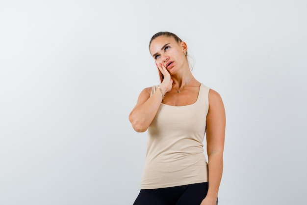 Mujer joven sosteniendo la mano en la mejilla en la camiseta sin mangas beige y mirando fatigado, vista frontal.