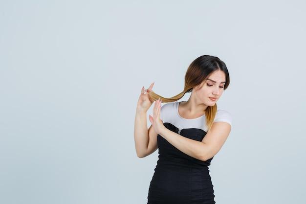 Mujer joven sosteniendo mechones de cabello y mostrando la señal de stop