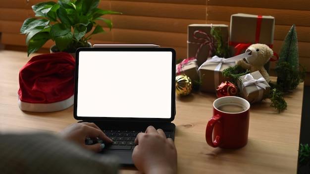 Mujer joven sosteniendo navegar por internet o hacer compras en línea con tableta digital en navidad.