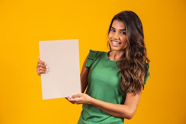 Mujer joven sosteniendo una pancarta con espacio para texto.