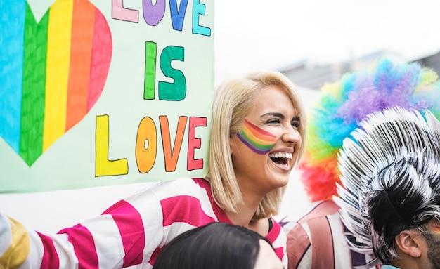 Mujer joven sosteniendo pancarta lgbt en un desfile del orgullo gay