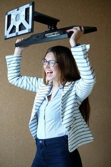 Mujer joven sosteniendo la pantalla del monitor con rabia
