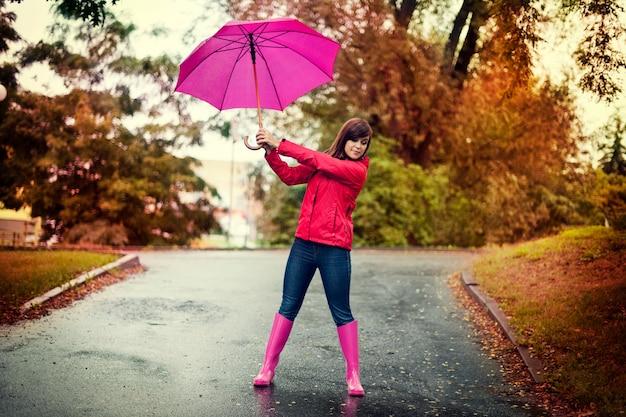 Mujer joven sosteniendo paraguas rosa en un parque