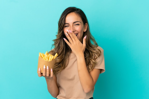 Mujer joven sosteniendo patatas fritas sobre fondo aislado feliz y sonriente cubriendo la boca con la mano