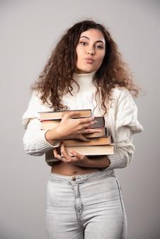 Mujer joven sosteniendo una pila de libros sobre una pared gris. foto de alta calidad