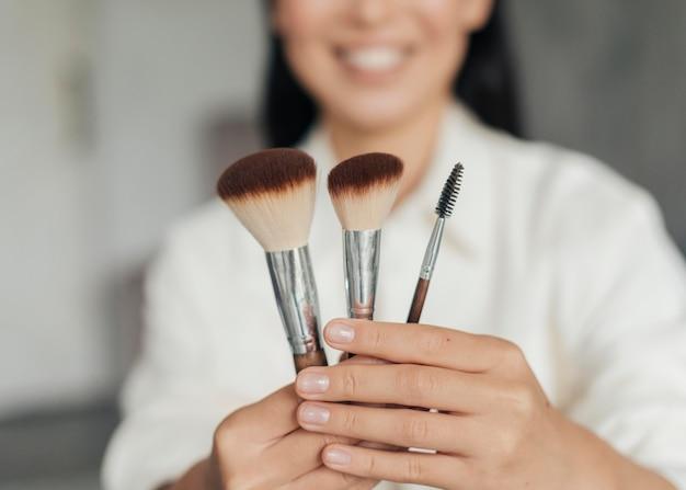 Mujer joven sosteniendo pinceles de maquillaje