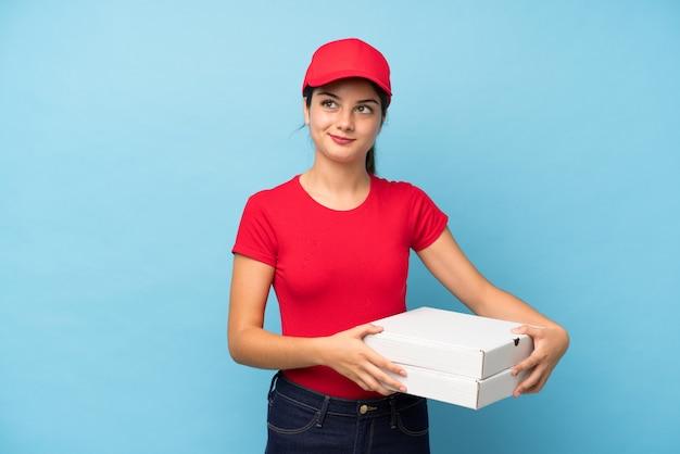 Mujer joven sosteniendo una pizza sobre pared rosa aislado de pie y mirando hacia el lado