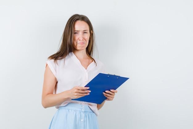 Mujer joven sosteniendo el portapapeles en camiseta, falda y mirando triste. vista frontal.