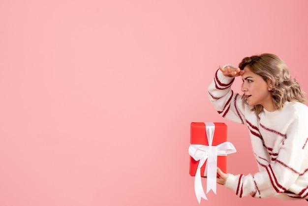 Mujer joven sosteniendo presente en rosa