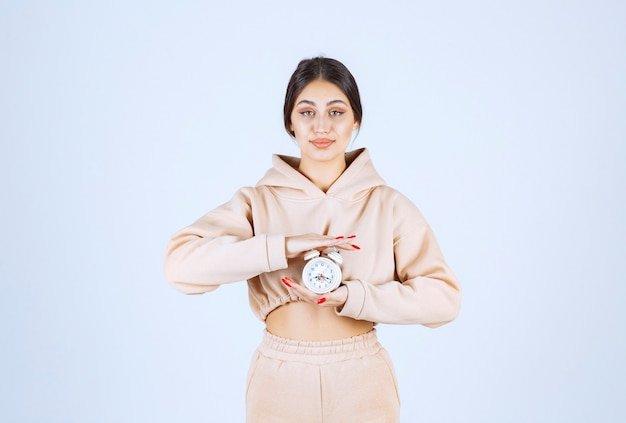 Mujer joven sosteniendo y promocionando un nuevo modelo de reloj despertador
