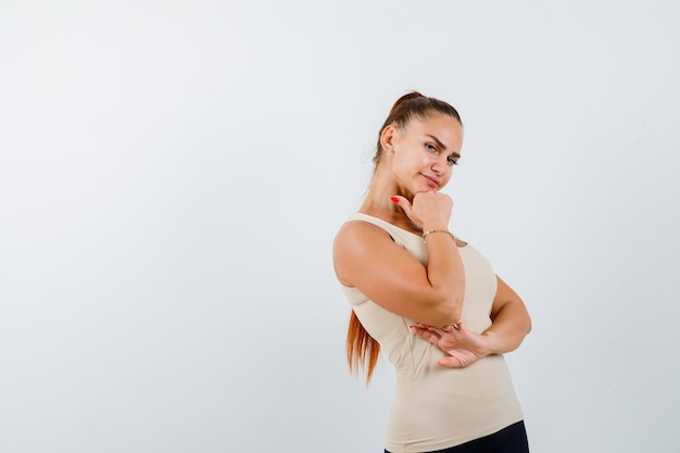 Mujer joven sosteniendo el puño debajo de la barbilla en la camiseta sin mangas beige y mirando confiado, vista frontal.