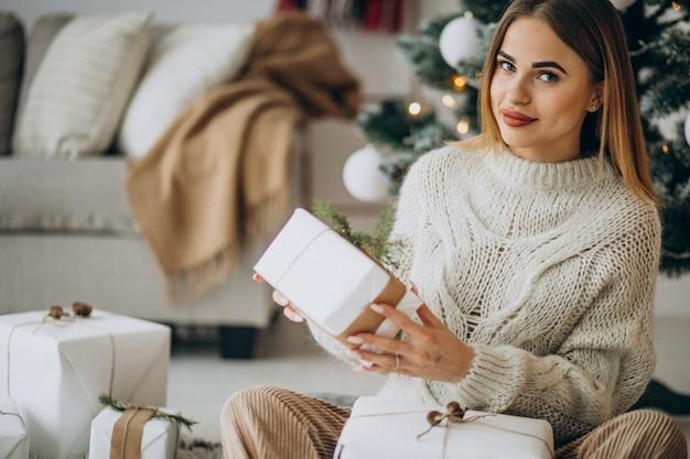 Mujer joven sosteniendo regalos de navidad y sentado bajo el árbol de navidad