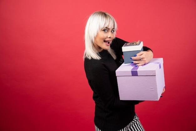 Mujer joven sosteniendo regalos en una pared roja.