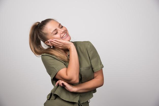 Mujer joven sosteniendo su mejilla en la pared gris.