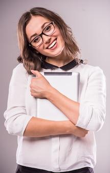 La mujer joven está sosteniendo la tableta digital y está sonriendo.