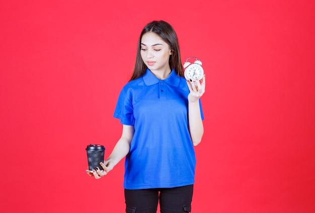 Mujer joven sosteniendo una taza de bebida desechable negra y un reloj despertador