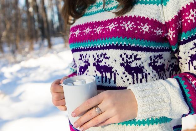 Mujer joven sosteniendo una taza de café con malvavisco