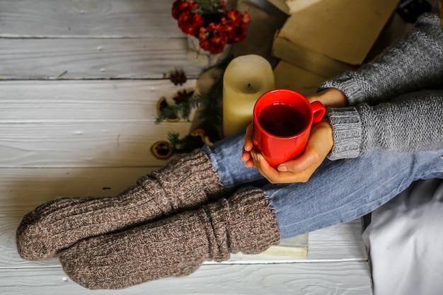Mujer joven sosteniendo una taza de té rojo en su dormitorio