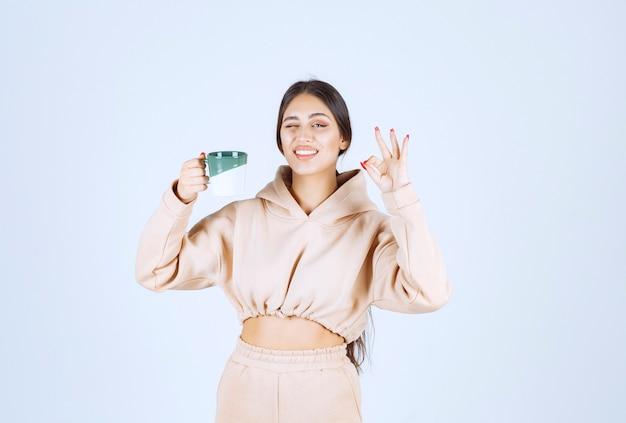 Mujer joven sosteniendo una taza verde y mostrando su satisfacción