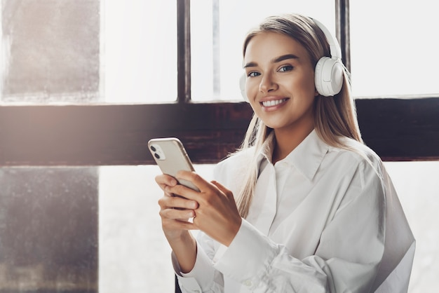 Mujer joven sosteniendo el teléfono inteligente en las manos, escuchando música en auriculares.