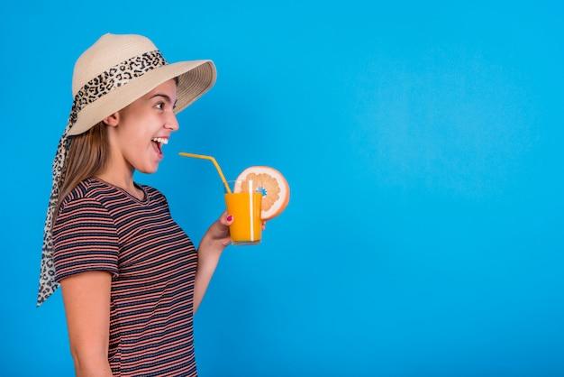 Mujer joven sosteniendo el vaso con jugo de naranja
