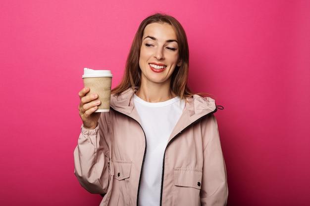 Mujer joven sosteniendo un vaso de papel mirándolo
