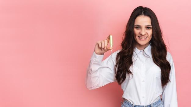 Una mujer joven sostiene un hisopo menstrual con un aplicador en sus manos para facilitar su uso. fondo rosa. espacio para texto