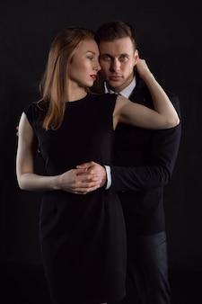 Mujer joven sostiene suavemente a su hombre por el cuello que suavemente pone su brazo alrededor de su cintura