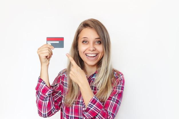 Una mujer joven sostiene una tarjeta de crédito de plástico en la mano y la señala con el dedo.