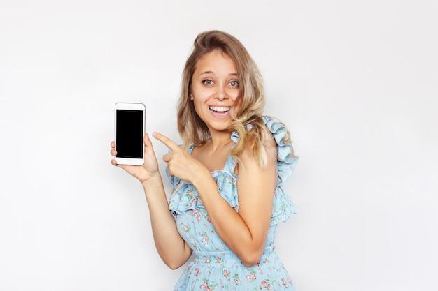 Una mujer joven sostiene un teléfono móvil en la mano y apunta a una pantalla negra que demuestra el espacio de la copia