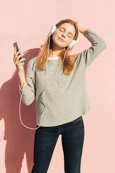 Mujer joven con su auricular en su cabeza escuchando música a través del teléfono móvil