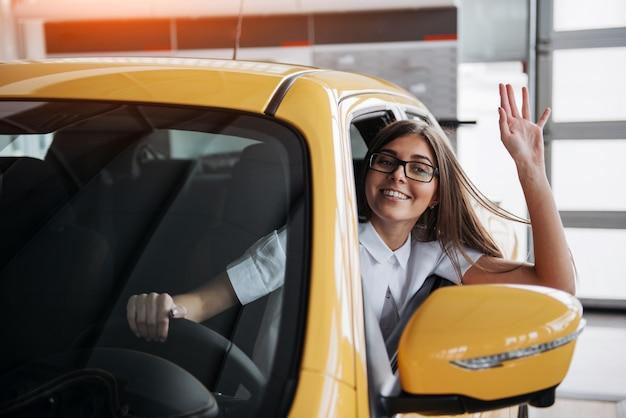 Mujer joven en su auto nuevo sonriendo