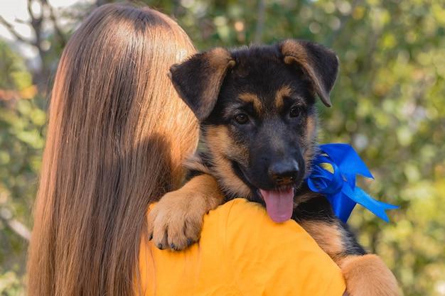 Mujer joven con su cachorro de pastor alemán en el hombro