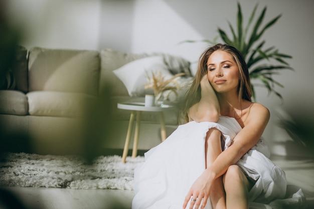 Mujer joven en su casa cubierta con una manta