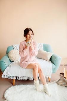 Mujer joven en su casa sentada en una silla moderna frente a la ventana, relajándose en su sala de estar, tomando café o té