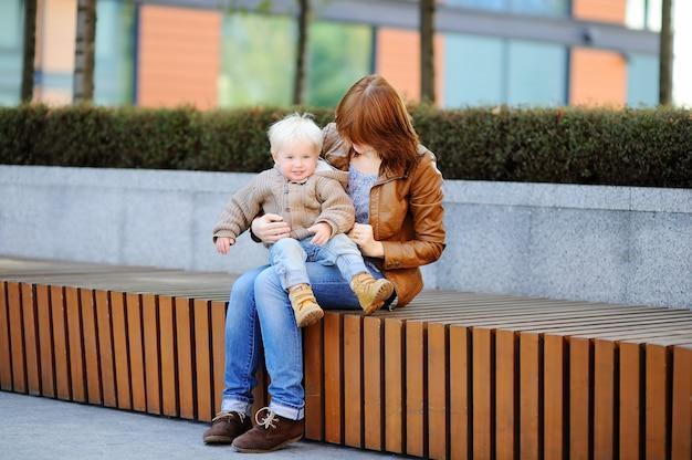 Mujer joven y su hijo lindo del niño que juegan al aire libre en el día soleado de la primavera o del otoño