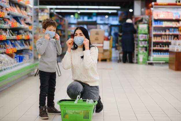 Mujer joven y su hijo con máscaras protectoras compran comida en un supermercado durante la epidemia de coronavirus o el brote de gripe
