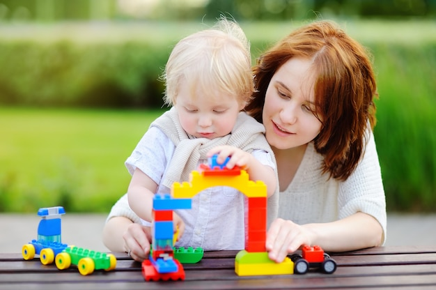 Mujer joven con su hijo pequeño jugando con coloridos bloques de plástico