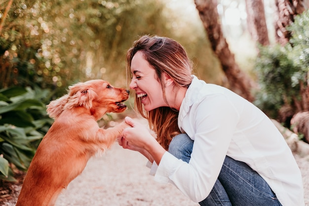 Mujer joven y su lindo cachorro de cocker spaniel al aire libre en un parque