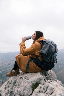 Mujer joven con su mochila sentada en la cima del pico de la montaña bebiendo el agua de una botella